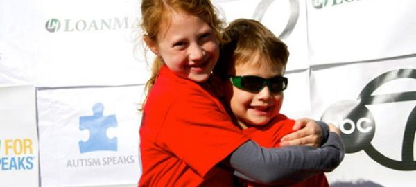 sister and brother hugging and smiling at autism event