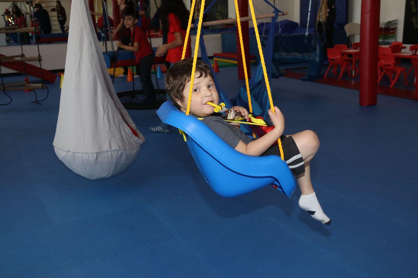 kid sitting in blue swing