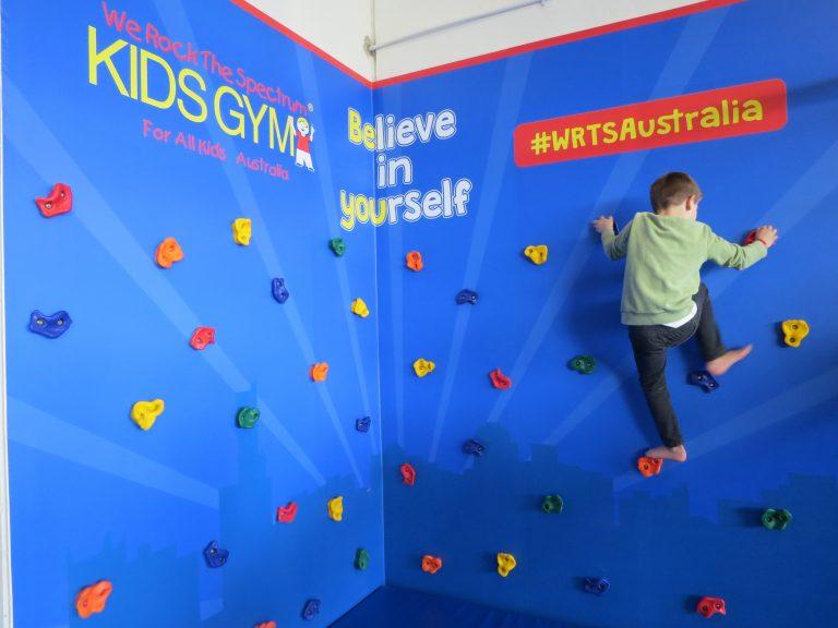 boy climbing we rock wall