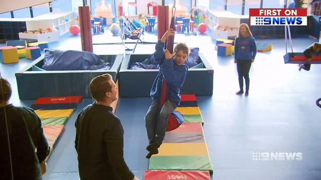 boy riding zip line indoor play gym