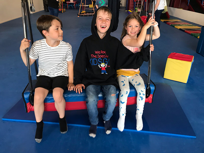 kids smiling on bolster swing