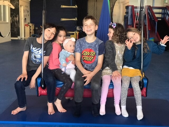 kids smiling sitting on bolster swing at gym