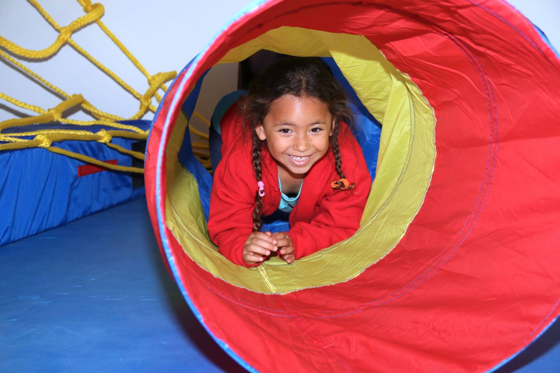 kid playing in tunnel smiling